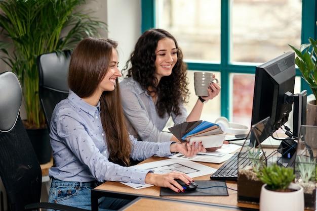 Zwei schöne designerinnen oder architekten lösen gemeinsam arbeitsaufgaben, während sie in einem modernen büro in der nähe des fensters arbeiten. kreative menschen oder werbegeschäftskonzept.