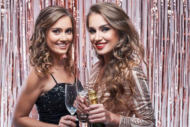 Zwei schöne elegante frauen, die champagner gegen funkelnde dekoration trinken