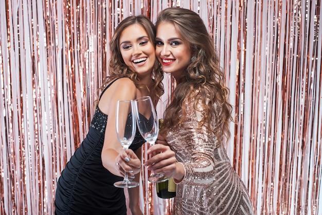 Zwei schöne elegante frauen, die champagnergläser klirren.