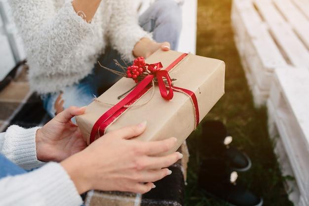 Zwei schöne frauen, die auf einer bank sitzen und in ihren händen geschenke halten, schließen ansicht