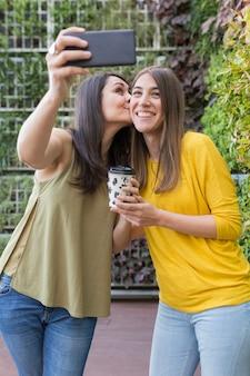 Zwei schöne frauen, die ein selfie mit handy nehmen. eine hält eine tasse kaffee und küsst ihre freundin. sie lachen. outdoor-lifestyle- und freundschaftskonzept
