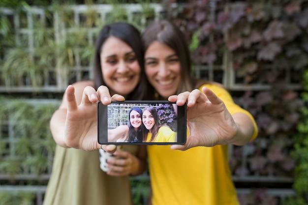 Zwei schöne frauen, die ein selfie mit handy nehmen. einer hält eine tasse kaffee. sie lachen. outdoor-lifestyle- und freundschaftskonzept