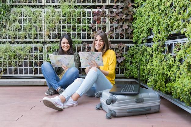 Zwei schöne frauen, die eine karte schauen. . sie lachen und suchen nach einem ort, an dem sie in den ferien bleiben können. draußen lifestyle und freundschaft. koffer und laptop dabei.