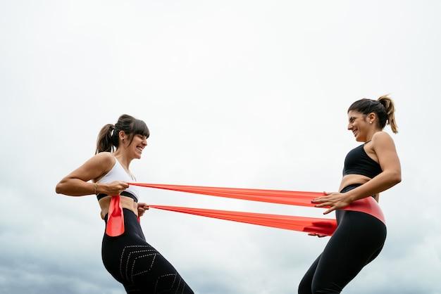 Zwei schöne frauen, die fitness mit einem gummiband auf einem weißen hintergrund tun