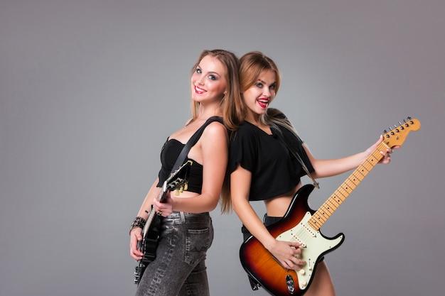 Zwei schöne frauen, die gitarren spielen