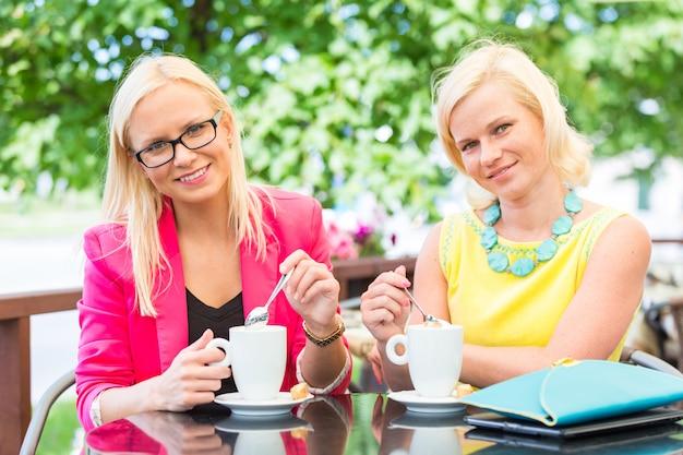 Zwei schöne frauen, die kaffee an der bar trinken