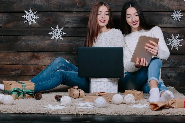 Zwei schöne frauen, die mit einem laptop und einem tablett auf dem boden sitzen, zwischen geschenken für weihnachten