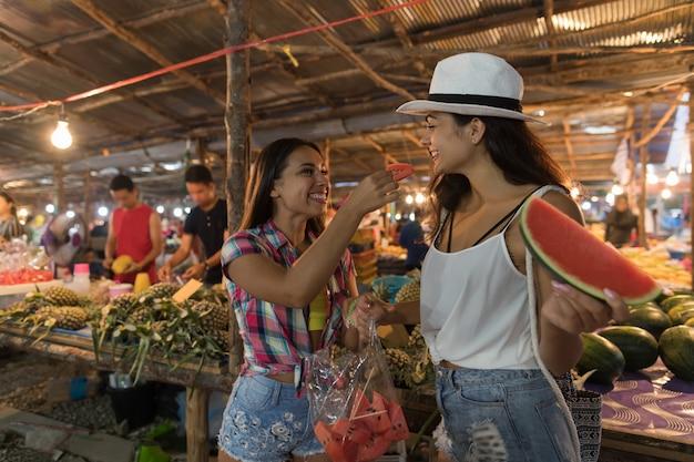 Zwei schöne frauen, die wassermelone auf traditionellem straßenmarkt in asien schmecken