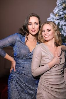 Zwei schöne frauen, die weihnachten zusammen mit modekleid feiern. weihnachten zu hause