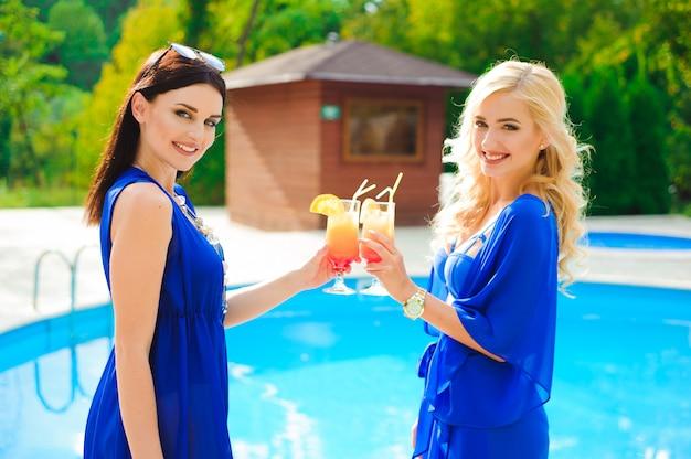 Zwei schöne frauen, die zusammen cocktails am swimmingpool haben.