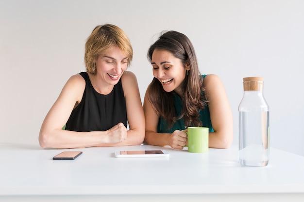 Zwei schöne frauen im büro auf der suche nach informationen auf tablet oder handy. weißer hintergrund. modernes bürokonzept. krug wasser auf dem tisch.