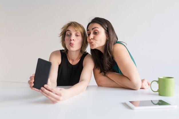 Zwei schöne frauen im büro, die ein selfie mit handy nehmen. weißer hintergrund. modernes bürokonzept