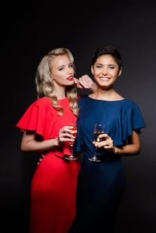 Zwei schöne frauen in den abendkleidern lächelnd, champagnerglas haltend