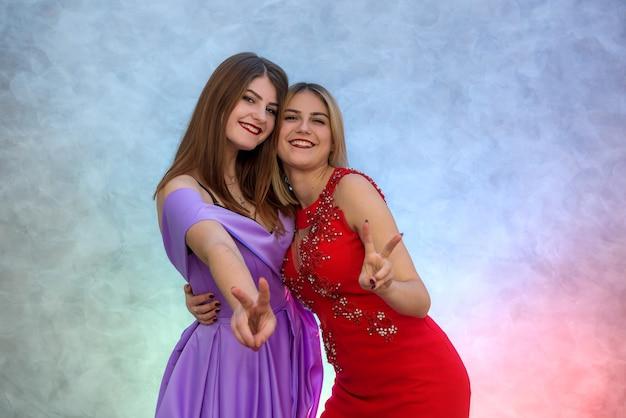 Zwei schöne frauen in eleganten kleidern feiern neujahr