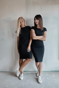Zwei schöne frauen in schwarzen kleidern