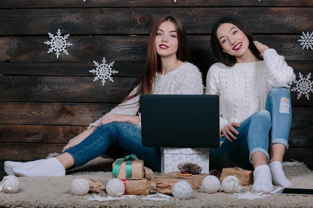 Zwei schöne frauen liegen mit einem laptop zwischen weihnachtsgeschenken auf dem boden