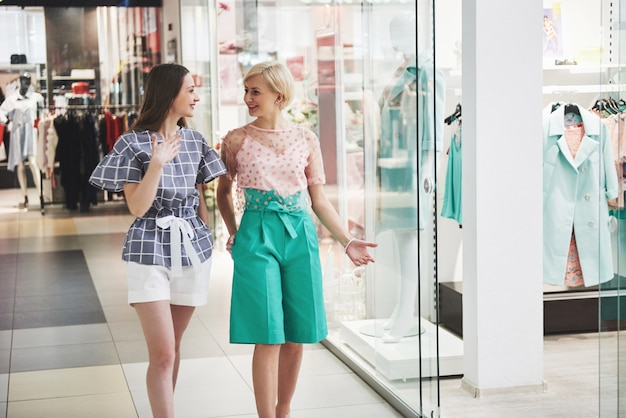 Zwei schöne frauen mit taschen, die sich mit lächeln beim gehen am bekleidungsgeschäft ansehen