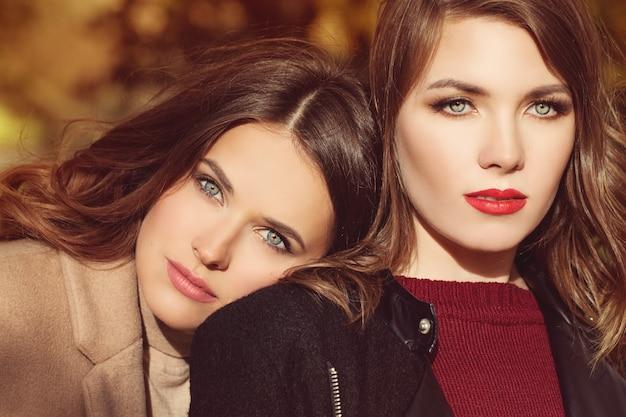 Zwei schöne frauen-mode-modelle mit make-up und frisur im freien nettes gesicht nahaufnahme