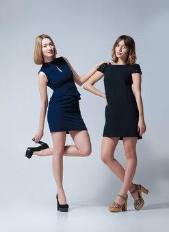 Zwei schöne frauen posieren in kleidern