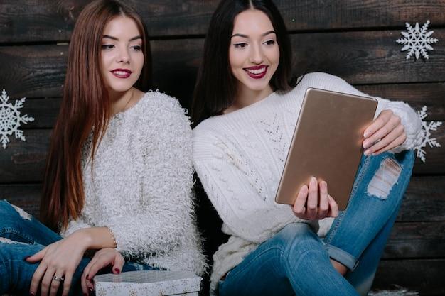 Zwei schöne frauen sitzen auf dem boden mit einer tablette