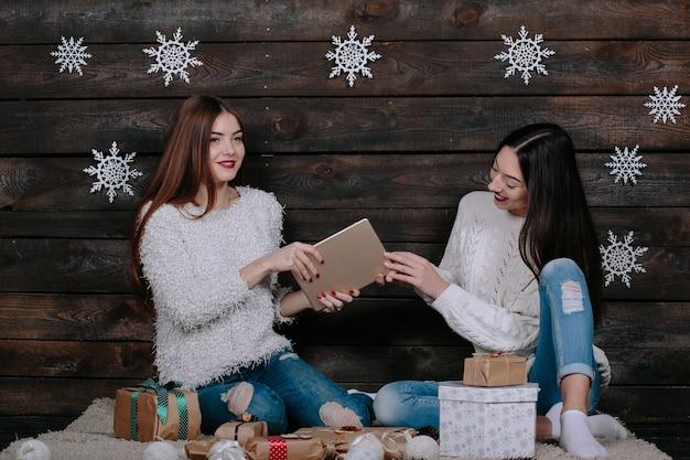 Zwei schöne frauen sitzen auf dem boden mit einer tafel, zwischen geschenken für weihnachten