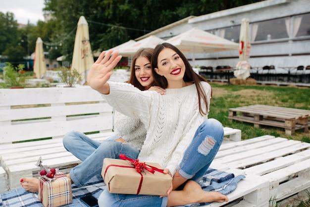 Zwei schöne frauen sitzen auf einer bank, halten geschenke in ihren händen und schauen