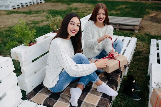 Zwei schöne frauen sitzen auf einer bank und halten in ihren händen geschenke