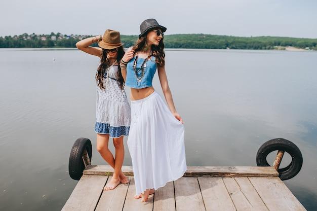 Zwei schöne freundinnen auf dem dock