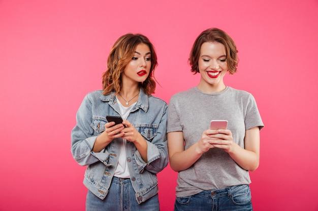 Zwei schöne freundinnen, die durch telefone plaudern.