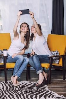 Zwei schöne freundinnen, die glücklich lächeln, lächeln zwischen den büchern zu hause