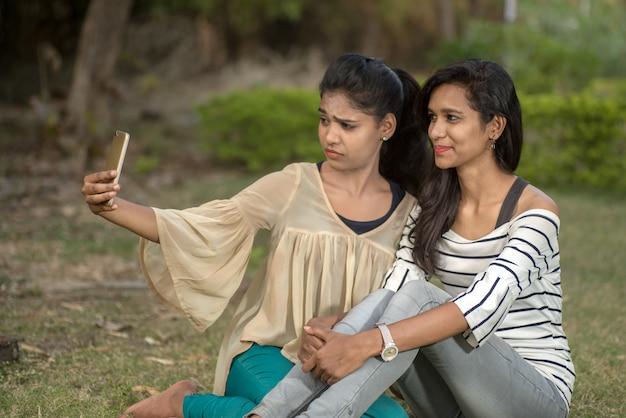 Zwei schöne freundinnen, die selfie mit smartphone im freien nehmen.