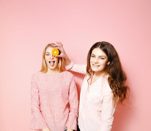 Zwei schöne freundinnen, die spaß auf rosa hintergrund haben.