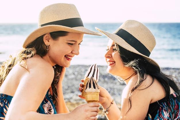 Zwei schöne freundinnen mit strohhut, die sich amüsieren, während der sommerferien kalte eistüten an einem ruhigen strand zu genießen. fröhliche frauen genießen eis auf sand vor der meereslandschaft