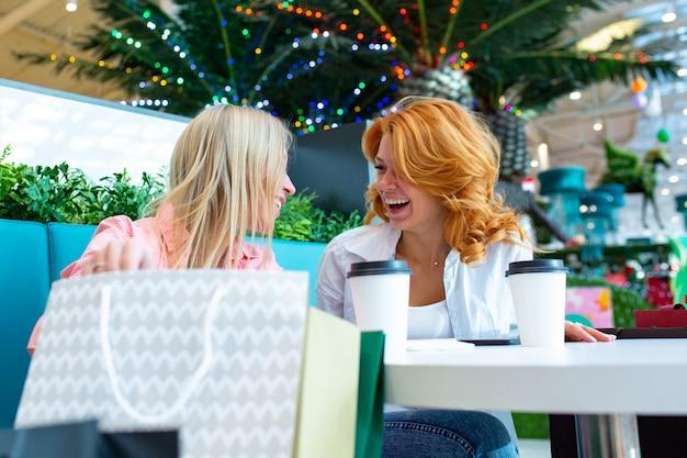 Zwei schöne freundinnen sitzen nach ihren einkäufen während des verkaufs in einem café