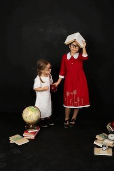 Zwei schöne freundinnen von schulmädchen stehen in der nähe einer tafel mit büchern