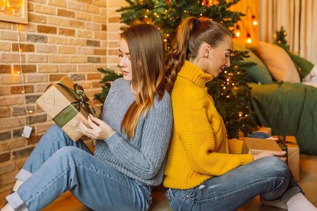 Zwei schöne fröhliche glückliche junge mädchen freundin geben weihnachtsgeschenke auf dem hintergrund eines neujahrsbaums zu hause