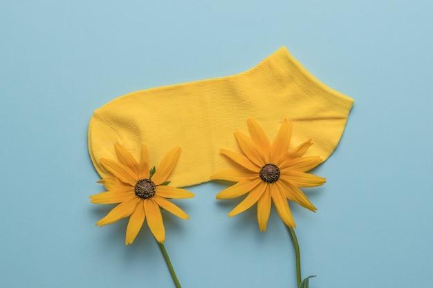Zwei schöne gelbe blumen und eine kurze sportsocke auf blauem grund. das konzept eines sommerurlaubs.