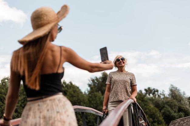 Zwei schöne glückliche frauenmama mit tochter in modischer sommerkleidung machen ein foto am telefon, selfie