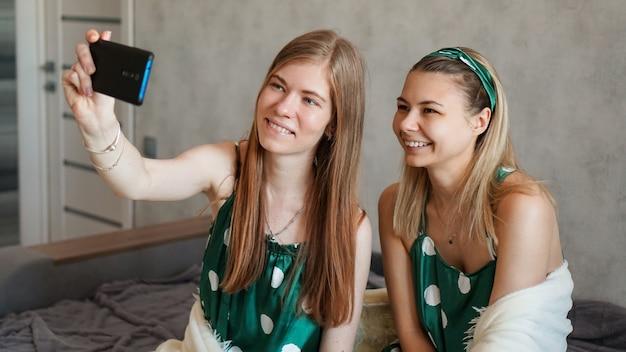 Zwei schöne glückliche freundinnen, die selfie mit smartphone auf pyjama-party nehmen
