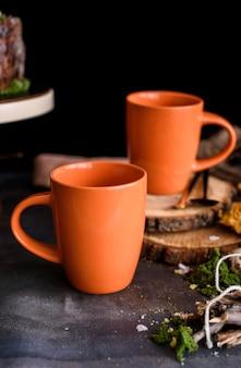 Zwei schöne große orange tassen für tee und getränke in einer schönen komposition.