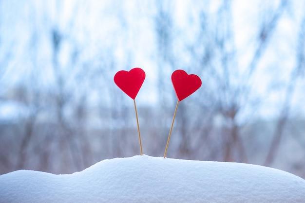 Zwei schöne herzen auf einem winterhintergrund