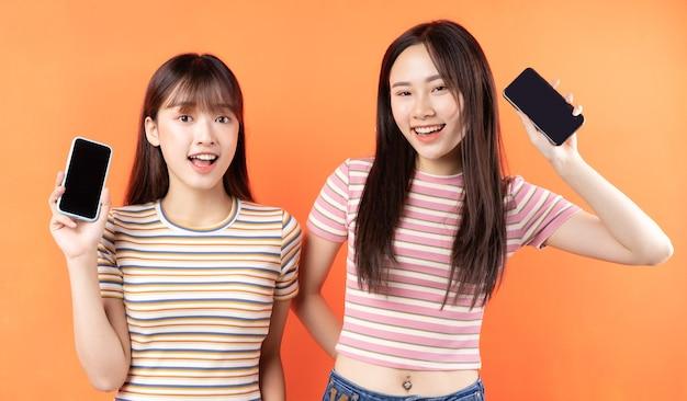 Zwei schöne junge asiatische mädchen benutzen handys an der orangefarbenen wand
