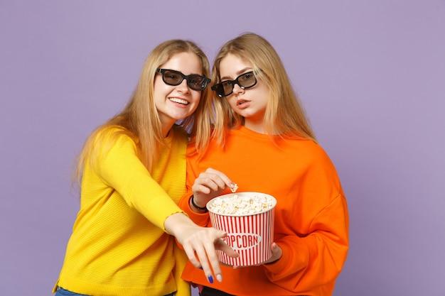 Zwei schöne junge blonde zwillingsschwestern mädchen in 3d-imax-brille, die filmfilme ansehen und popcorn isoliert auf pastellvioletter blauer wand halten. menschen-familien-lifestyle-konzept.