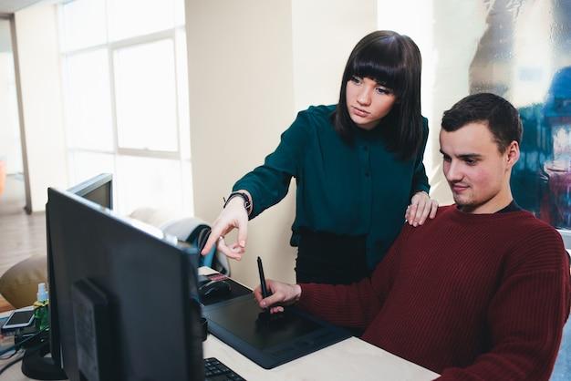 Zwei schöne junge büroangestellte, die einen computermonitor betrachten und das projekt diskutieren. die situation im büro.