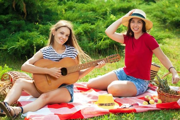 Zwei schöne junge frauen auf einem picknick, das eine gitarre spielt und spaß hat