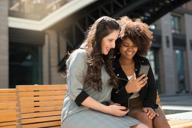 Zwei schöne junge frauen auf einer bank im sommer mit einem telefon