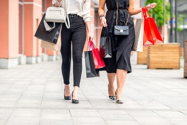Zwei schöne junge frauen, die am einkaufszentrum mit taschen gehen