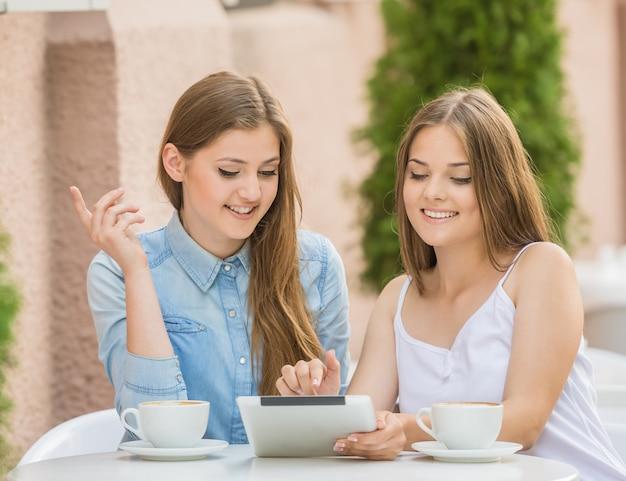 Zwei schöne junge frauen, die am sommercafé sitzen.