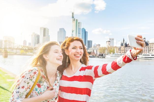 Zwei schöne junge frauen, die ein selfie auf frankfurt machen