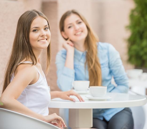 Zwei schöne junge frauen, die für kaffee sich treffen.